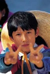 Young boy raising peace symbol on both hands demonstrating alternatives to aggression and violence